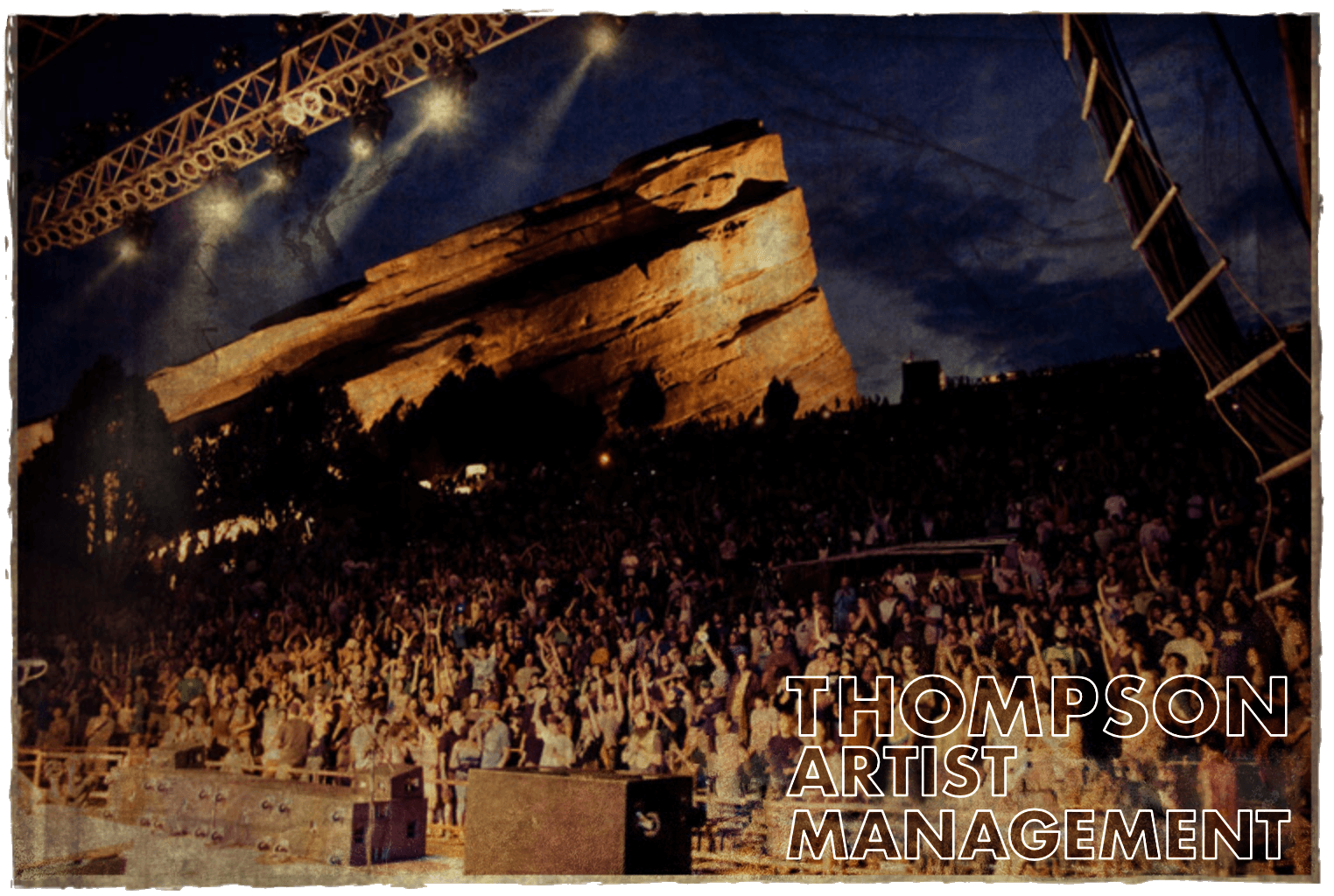 A dramatic nighttime stage view photo of a concert crowd.